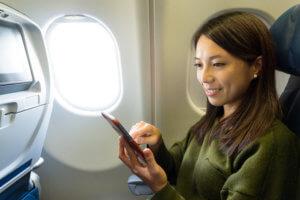 機内でWi-Fiに接続して、スマホを使用する女性