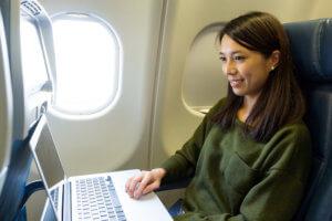 飛行機内でパソコンを使用する女性