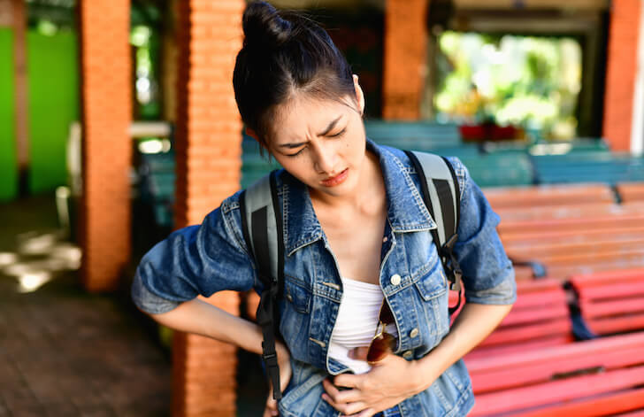 旅行中に腹痛の女性