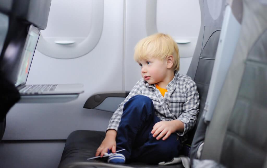 飛行機の座席で映画を観る男の子