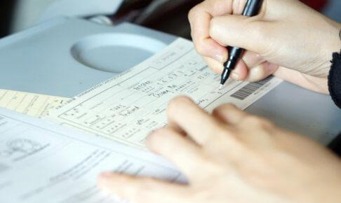 イミグレーションカードを書く女性の手