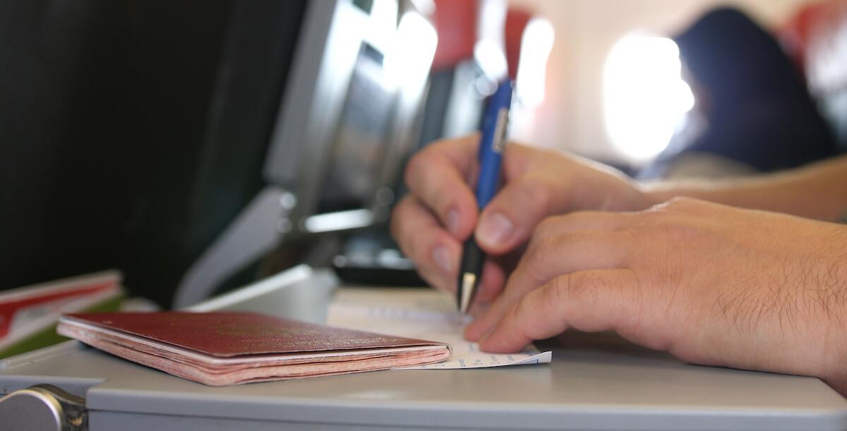 テーブルの上で入国カードを記入している男性の手