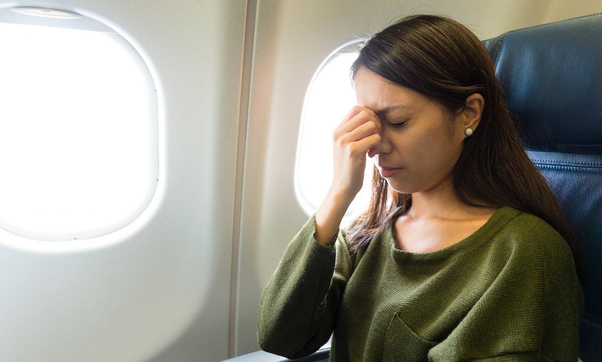 飛行機内でめまいを感じている女性