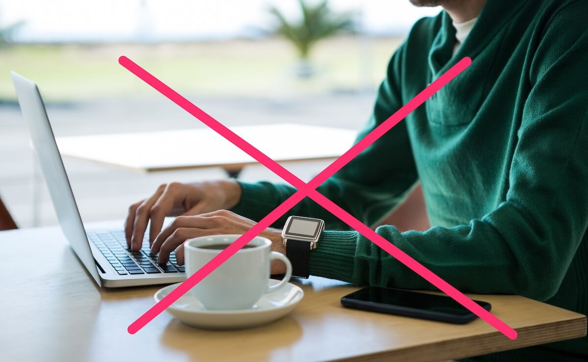 テーブルの上に置かれたスマホとパソコンを触る男性