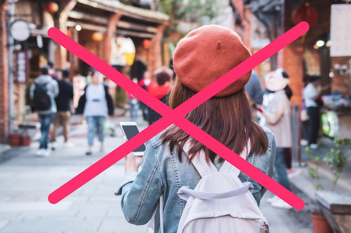 観光地で歩きスマホをする女性