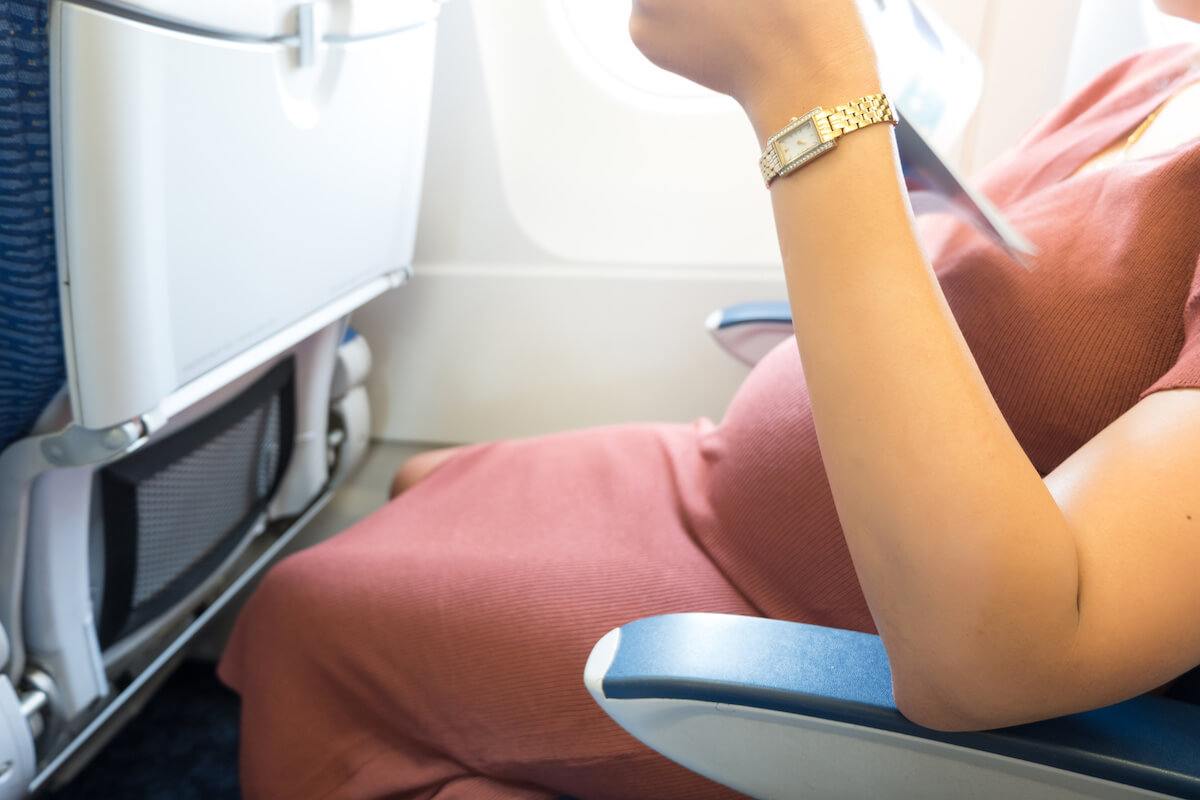 ゆったりした服を着て、飛行機の座席に座る妊婦さん