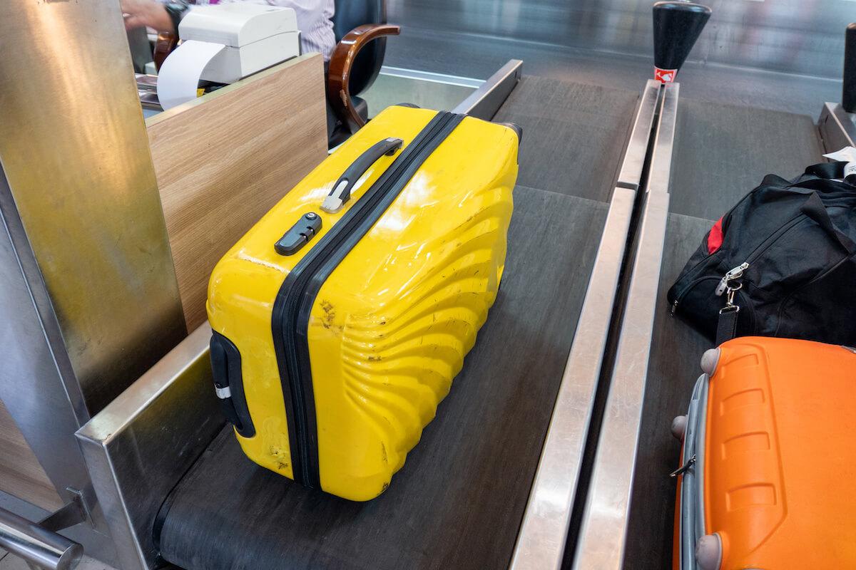 空港カウンターのベルトコンベアーの上に置かれた荷物