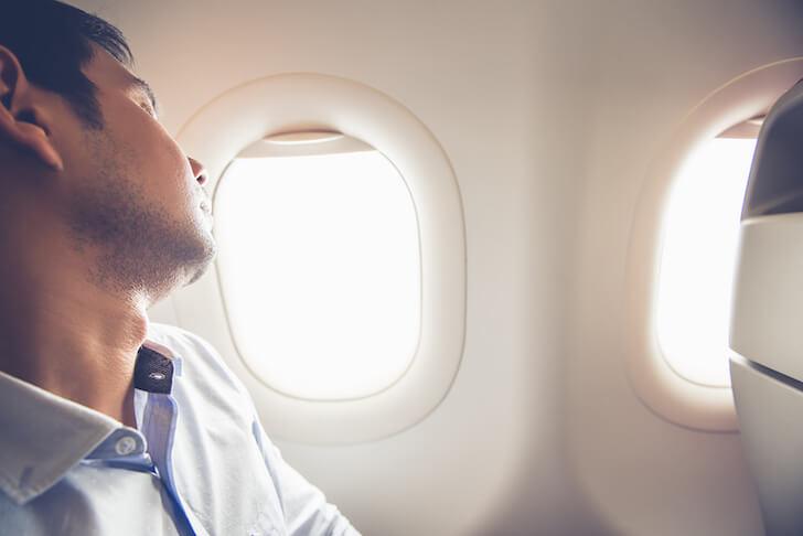 飛行機に乗る疲れている男性