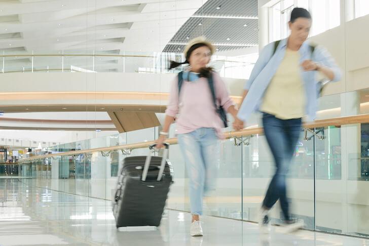 飛行機に乗り遅れそうで、空港を走るカップル